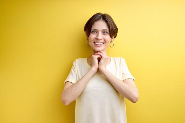 Ritratto di donna adulta graziosamente sorridente in posa alla telecamera, isolato su sfondo giallo, vestito casualmente. donna adorabile sognante con i capelli corti che si tiene per mano insieme