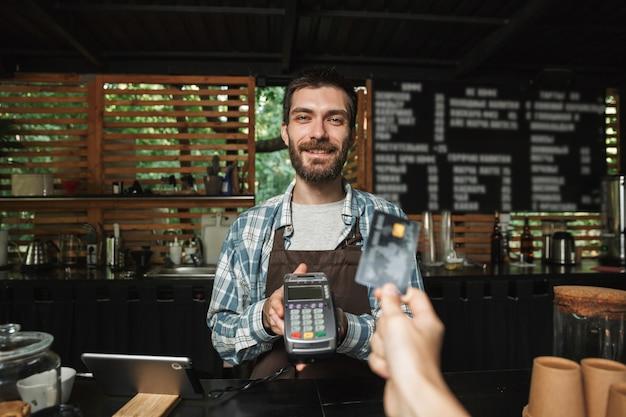 Ritratto di un affabile barista che indossa un grembiule che prende la carta di credito dal cliente mentre lavora in un caffè di strada o in una caffetteria all'aperto