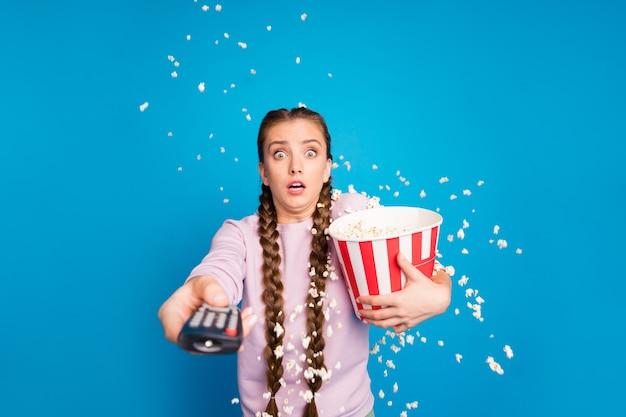 Ritratto di ragazza giovane impaurito con trecce trecce guarda tv tenere la scatola con popcorn vedere la serie horror vuole cambiare canale pop corn volare cadendo soffiando nel vento isolato sfondo di colore luminoso