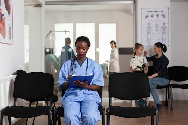 Ritratto di assistente afroamericano che esamina la macchina fotografica mentre scrive il servizio di supporto sanitario ...