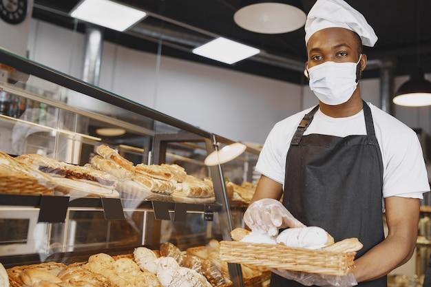 Ritratto di panettiere afroamericano con pane fresco al forno. pasticcere che tiene piccola pasticceria.