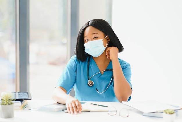 Ritratto del medico della bella donna afroamericana nella mascherina medica che guarda l'obbiettivo. primo piano medico femminile nella protezione delle vie respiratorie.