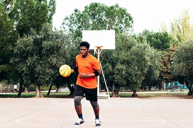 Ritratto di un ragazzo nero afro-americano che gioca a basket su un tribunale urbano.
