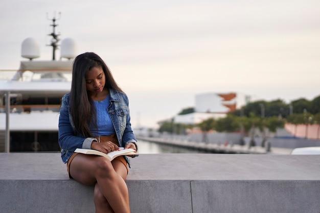 Ritratto di una donna nera afroamericana che legge un libro seduto su una panchina in strada.