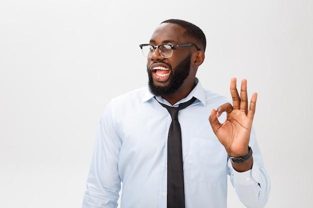 Ritratto dell'uomo di affari dell'afroamericano che sorride e che mostra il segno giusto.
