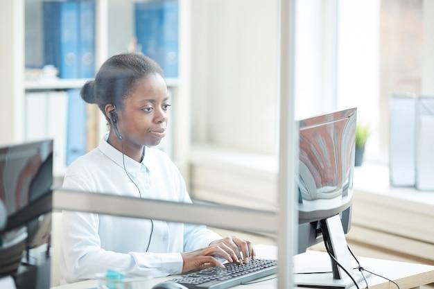 Ritratto di donna d'affari afro-americana che indossa l'auricolare durante l'utilizzo del computer sul posto di lavoro, girato da dietro la parete di vetro