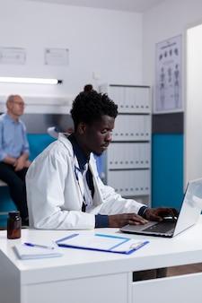 Ritratto di medico afroamericano seduto alla scrivania utilizzando laptop