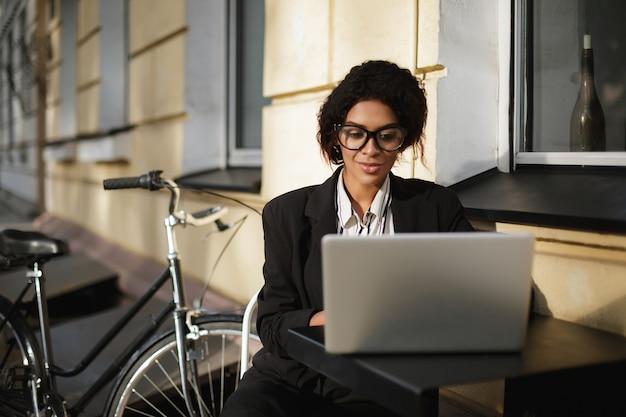 Ritratto di ragazza afroamericana con gli occhiali seduto al tavolo del bar e lavorando sul suo computer portatile
