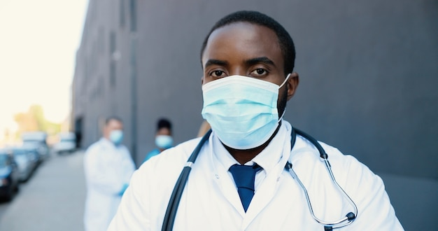 Ritratto di medico afroamericano uomo bello in maschera medica e con lo stetoscopio che guarda l'obbiettivo. chiuda in su del medico maschio nella protezione respiratoria. medici di razze miste sullo sfondo.