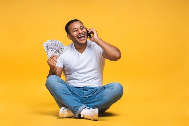 Ritratto di giovane nero indiano afroamericano seduto sul pavimento che tiene banconote in dollari isolate su sfondo giallo. utilizzo del telefono cellulare.