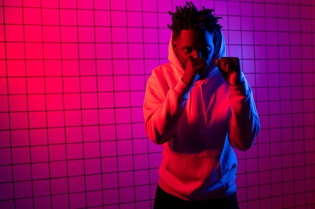 Ritratto di un uomo afroamericano in una felpa con cappuccio su uno sfondo al neon sfondo rossoblu foto di alta qualità