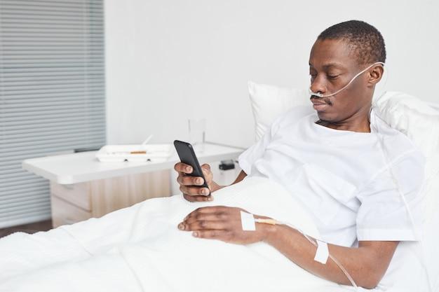 Ritratto di uomo afro-americano nel letto d'ospedale e utilizza lo smartphone con tubi di integrazione di ossigeno, spazio copia