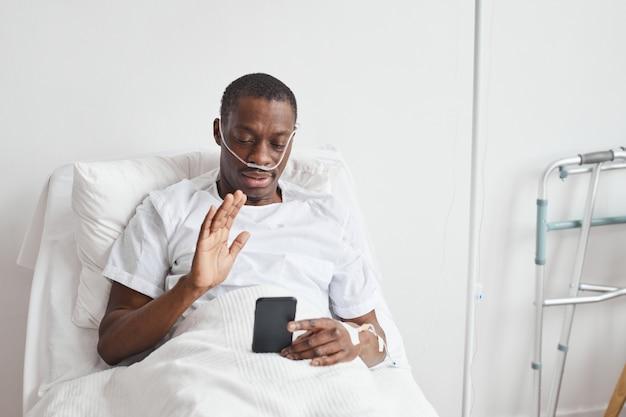 Ritratto di uomo afro-americano che parla tramite videochiamata in ospedale e saluta la telecamera mentre giace nel letto bianco, copia spazio