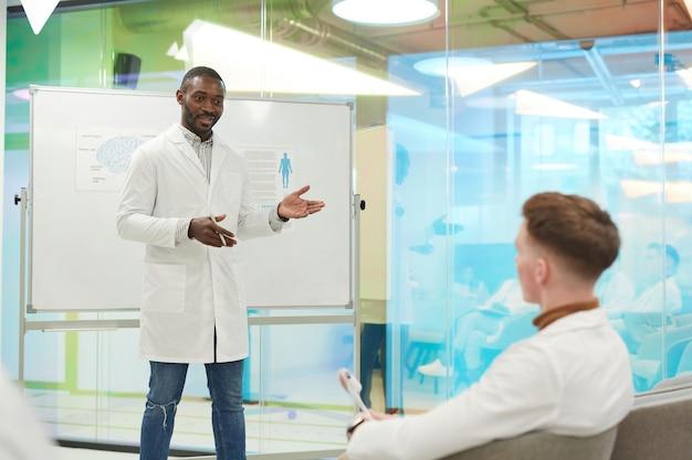 Ritratto di uomo afro-americano in piedi davanti alla lavagna mentre fa una presentazione durante il seminario medico al college, copia spazio