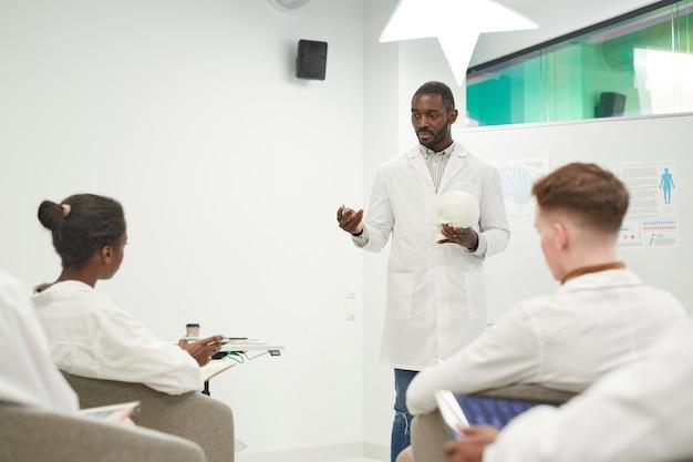 Ritratto di un uomo afro-americano in piedi davanti alla lavagna mentre tiene un seminario sulla medicina al college, copia spazio