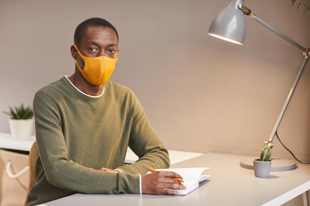 Ritratto di uomo afro-americano che indossa la maschera per il viso e guardando la fotocamera mentre è seduto alla scrivania in ufficio a casa, copia dello spazio