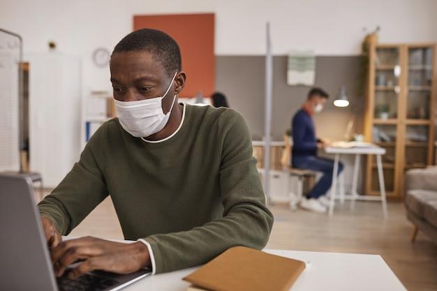 Ritratto di uomo afro-americano che indossa la maschera e utilizzando laptop mentre si lavora alla scrivania in ufficio, copia dello spazio
