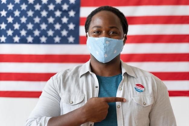 Ritratto di uomo afroamericano con maschera medica il giorno della registrazione degli elettori