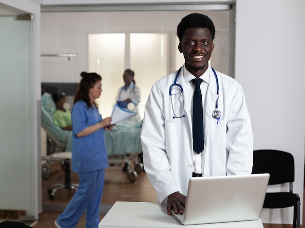 Ritratto di uomo afroamericano che lavora alla scrivania del reparto ospedaliero