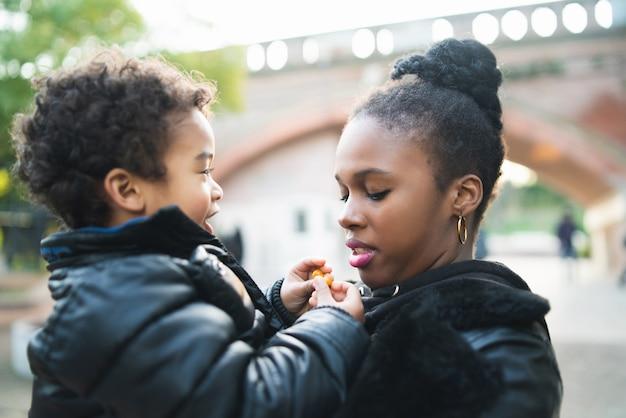 Ritratto di una madre afroamericana con suo figlio in piedi all'aperto nel parco, divertendosi. famiglia monoparentale.