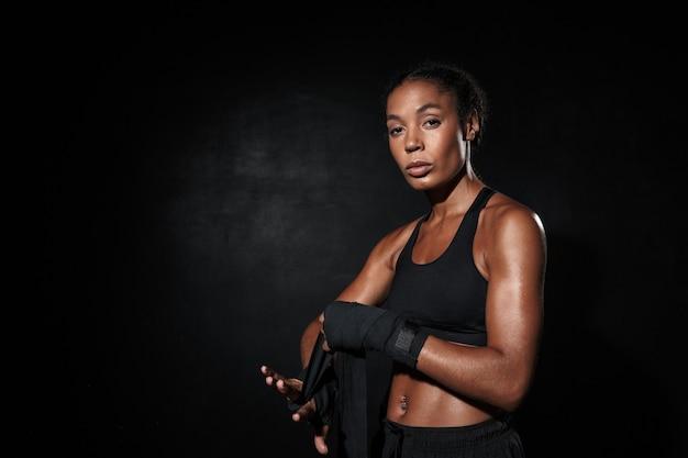 Ritratto di donna afroamericana in abiti sportivi che indossano fasce per le mani da boxe isolate su nero