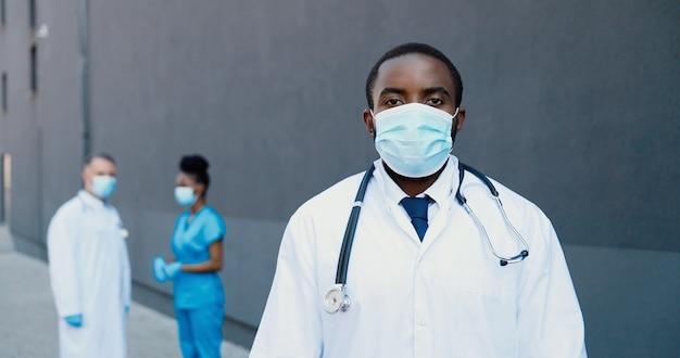 Ritratto del medico del giovane afroamericano nella mascherina medica e con lo stetoscopio che guarda l'obbiettivo. primo piano medico maschio in protezione respiratoria. medici multietnici sullo sfondo. colpo di dolly.