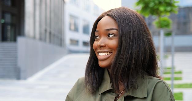 Ritratto di giovane donna graziosa afroamericana in piedi in via della città e sorridendo con gioia alla telecamera.