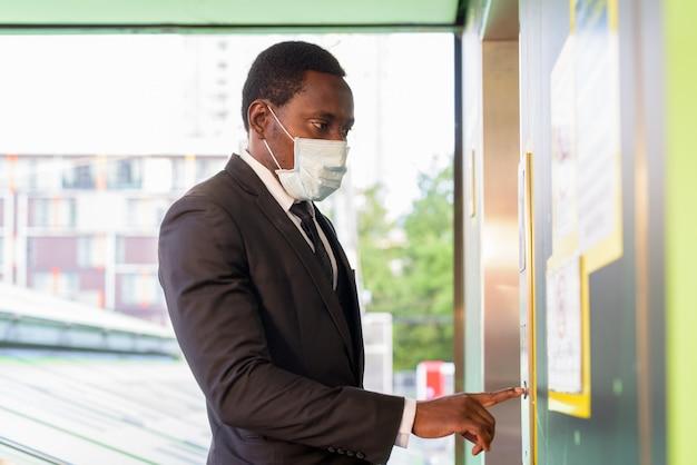 Ritratto dell'uomo d'affari africano con la maschera che preme il bottone dell'elevatore alla stazione ferroviaria all'aperto