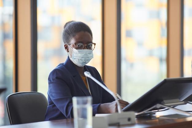 Ritratto di imprenditrice africana in occhiali da vista e in maschera protettiva guardando mentre è seduto al tavolo nella sala riunioni