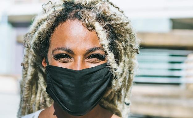 Ritratto di ragazza africana con i dreadlocks biondi che indossa una maschera protettiva per la prevenzione del coronavirus