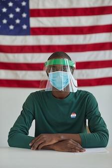 Ritratto di uomo africano in maschera protettiva seduto al tavolo durante il giorno delle elezioni con la bandiera americana in background