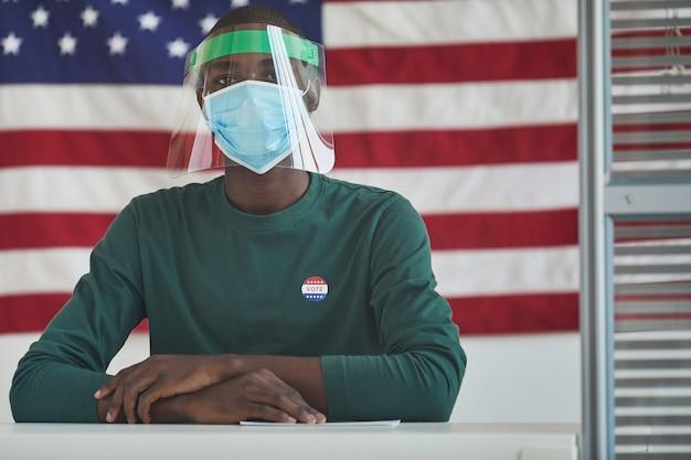 Ritratto di uomo africano in maschera protettiva seduto al tavolo e con la bandiera americana sullo sfondo