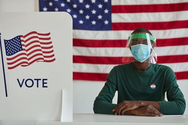 Ritratto di uomo africano in maschera protettiva seduto al tavolo e lavorando nel voto al seggio elettorale americano