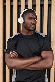 Ritratto di uomo muscoloso africano in piedi con le braccia incrociate all'aperto e ascoltando musica in w...
