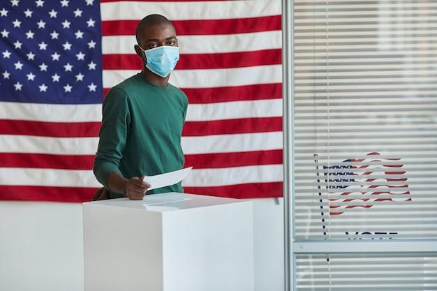 Ritratto di elettore africano in maschera protettiva che vota al seggio elettorale americano durante la pandemia