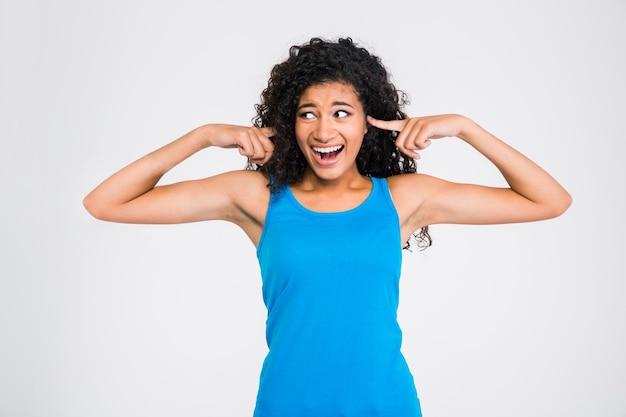 Ritratto di donna africana che si copre le orecchie con un dito e urla isolato