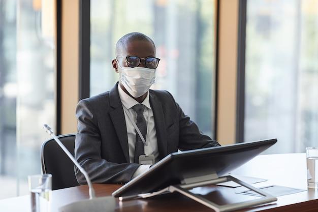 Ritratto di giovane uomo d'affari africano in maschera protettiva guardando seduto alla conferenza di lavoro