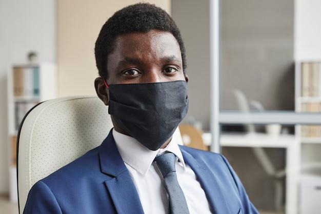 Ritratto di giovane imprenditore africano in maschera protettiva mentre è seduto in ufficio