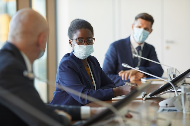 Ritratto di giovane imprenditrice africana in maschera protettiva guardando mentre è seduto alla riunione con i suoi colleghi