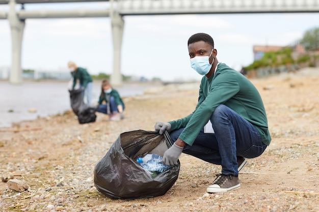 Ritratto di giovane africano in maschera protettiva che guarda l'obbiettivo mentre si mette la spazzatura nel sacco sulla riva del fiume