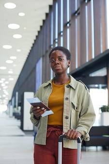 Ritratto di giovane donna africana in piedi con i bagagli e tenendo i biglietti aerei che guarda in aeroporto