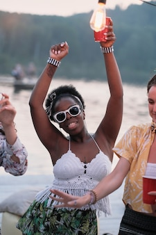 Ritratto di giovane donna africana in occhiali da sole, bere birra e ballare durante la festa all'aperto