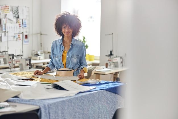 Ritratto di sarta afroamericana con strumenti in piedi al tavolo da taglio
