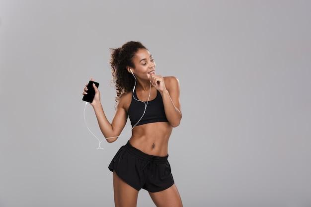 Ritratto di una sportiva felice afro americana isolata su sfondo grigio, ascoltando musica con gli auricolari, tenendo il telefono cellulare, ballando