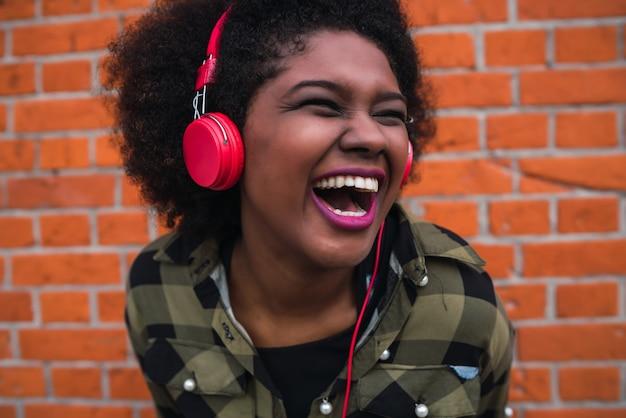Ritratto della donna latina afroamericana che sorride e che ascolta la musica con le cuffie contro il muro di mattoni. all'aperto.