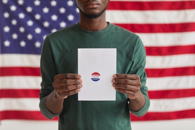 Ritratto di uomo afro-americano che tiene la scheda elettorale con segno di voto mentre levandosi in piedi contro la bandiera americana