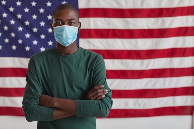 Ritratto di uomo afro-americano in maschera protettiva in piedi con le braccia incrociate e contro la bandiera americana