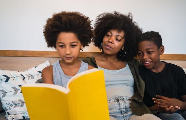 Ritratto della madre afroamericana che legge un libro ai suoi figli a casa