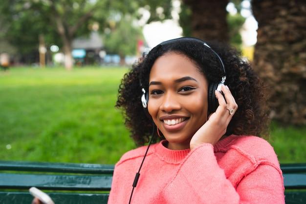 Ritratto di donna afroamericana sorridente e ascoltando musica con le cuffie nel parco. all'aperto.
