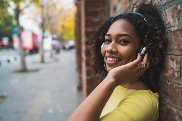 Ritratto di donna afroamericana sorridente e ascolto di musica con le cuffie in strada. all'aperto.